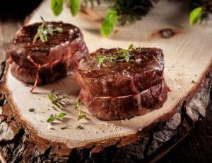 close up of two roasted venison steak filets seasoned with fresh herbs and served on rustic wood plank