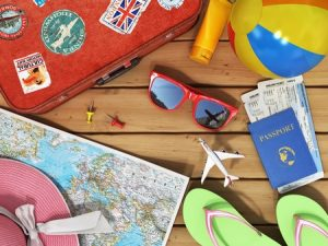 sunglasses, world map, beach shoes, sunscreen, passport, planeickets, beach ball, hat and old red suitcase for travel on the wood background.